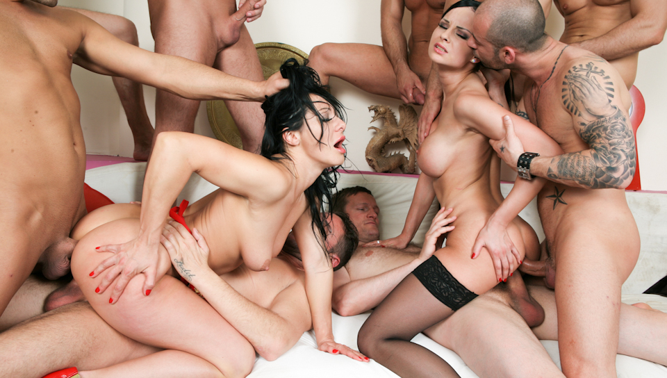 Two gorgeous girls participate in an eight man gang bang.