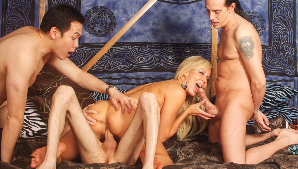 Hairy blonde cunt gets banged by three cocks on a huge bed.
